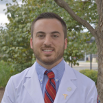 Benjamin Gordon, UIC MD/PhD Student photo wearing a lab coat outdoors