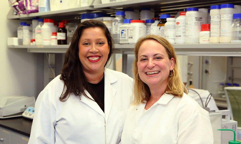 Two women researchers with white shirts in a lab smiling.