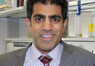 Ajay Maker wearing a suit and tie in his laboratory