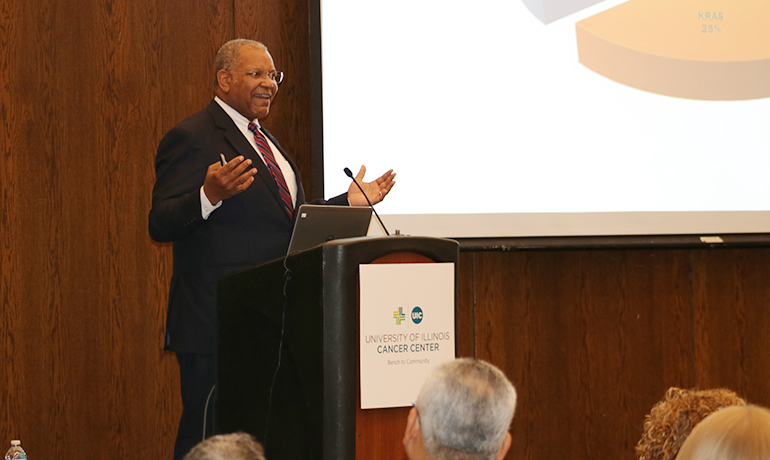 Brawley speaking in a UI Cancer Center seminar on a microphone podium.