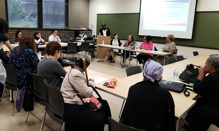 People sitting in a classroom for a CHER forum panel 2019.