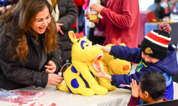 Woman and two boys playing with a yellow and blue stuffed animal.