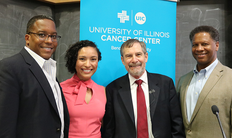Men and women researchers with UI Cancer Center banner in background.