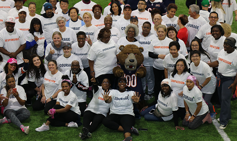 UI Cancer Center staff and researchers with Chicago Bears mascot in football field.