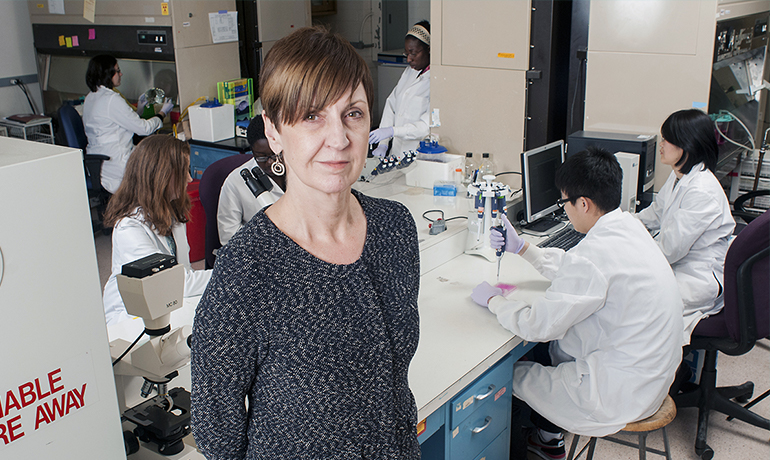 Judy Bolton close up with researchers in the back working in a lab.