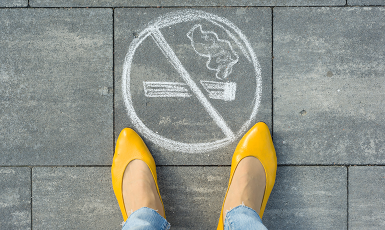 No smoking sign painted on concrete floor with white chalk next to yellow woman shoes.
