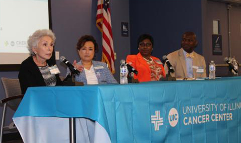 Three women and a man speaking on microphone and sitting down by a blue table.