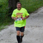 man running by the woods with a running number on his yellow shirt.