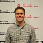 Mark Maienschein-Cline, PhD photo in front of a UIC step and repeat background